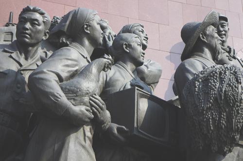 На монументе отцу и сыну несут кто что, а эта тетушка телевизор. Там всего две программы и обе понятно о чем